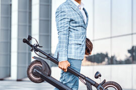 Elegant man is holding electro scooter